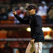 24 February 2018: The San Diego State Aztec baseball team competes in day two of the Tony Gwynn legacy tournament against #4 Arkansas. San Diego State Aztecs pitching coach Sam Peraza (26) signals to the bullpen for another relief pitcher in the top of the ninth inning. The Aztecs dropped a close game to the Razorbacks 4-2. <br /> More game action at sdsuaztecphotos.com