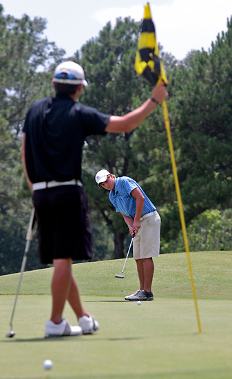 Chris Whittington, left, holds the flagstick while Chris Ingram putts at the Clear Creek Golf Course during the Warren County Golf Championship on Sunday, July 31, 2011. Whittington placed first in the tournament and Ingram placed second. (Bryant Hawkins/The Vicksburg Post)