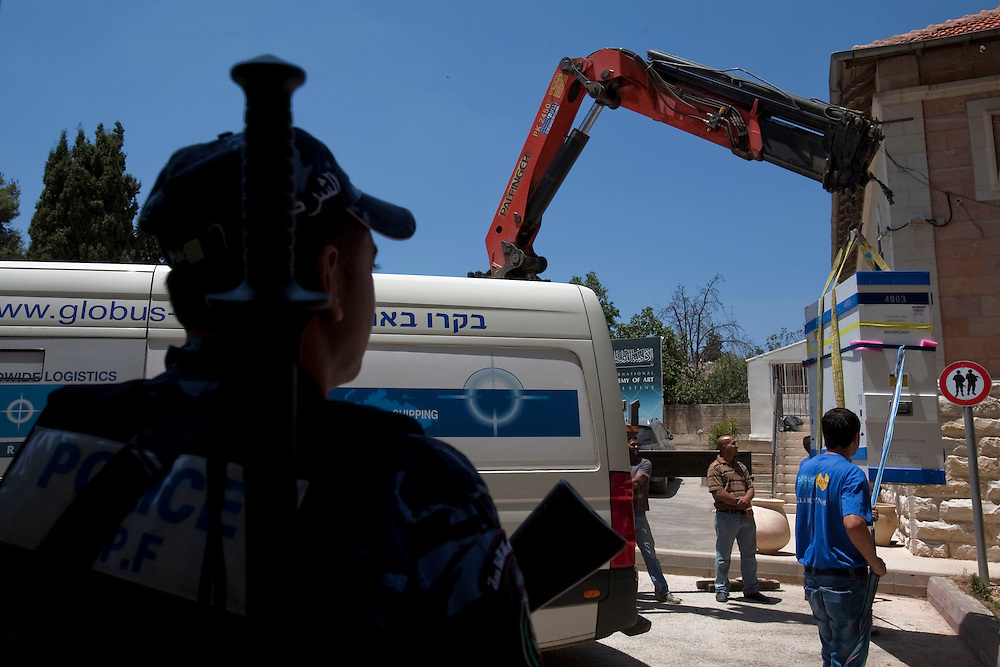 A Palestinian policer stands guard as workers move the Picasso paint to to the International Academy of Art of Palestine on June 19, 2011 in Ramallah...Photo by Olivier Fitoussi / Die Zeit