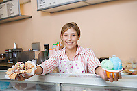 Portrait of young woman serving ice creams