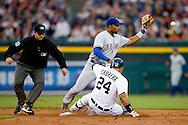 May 23, 2014; Detroit, MI, USA; Detroit Tigers first baseman Miguel Cabrera (24) slides in safe ahead of the throw to Texas Rangers shortstop Elvis Andrus (1) after he hits an RBI double in the third inning at Comerica Park. Mandatory Credit: Rick Osentoski-USA TODAY Sports