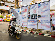 29 JANUARY 2014 - BANGKOK, THAILAND: Traffic passes a sign in Thai and English outlining the alleged ethical breaches of the Pheu Thai government under Prime Minister Yingluck Shinawatra, who is widely considered to be a puppet of her brother, exiled former Prime Minister Thaksin Shinawatra. Thais are supposed to vote Sunday, February 2 in a controversial national election. Anti-government protestors have vowed to disrupt the election. One person was killed and several injured in election related violence during early voting on Sunday Jan. 25. The ruling Pheu Thai party is widely expected to win the election, which is being boycotted by the Democrats and opposition parties.      PHOTO BY JACK KURTZ