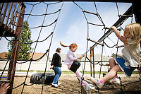 JEROME A. POLLOS/Press..Kimmie McHatton climbs on a play set Monday while Elizabeth Scarlett swings next to Kim Williams, the administrator of Noah's Ark Learning Center in Coeur d'Alene. Williams, 26, attended the day care center when she was a child and now the center is celebrating its 25th anniversary.