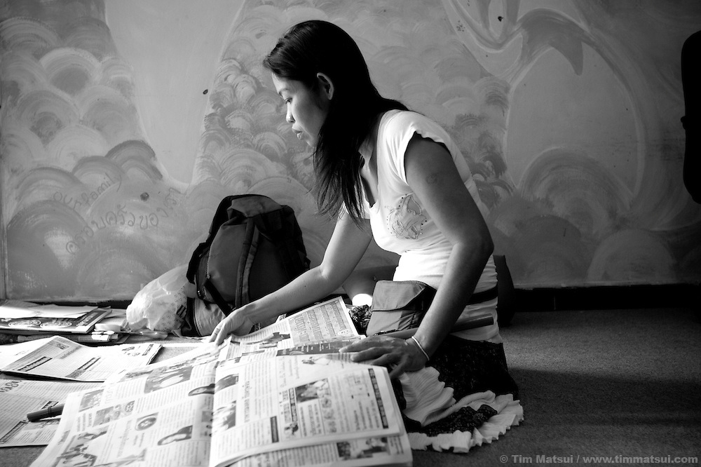 "ID: Wasana reads the paper. >> At the Chiang Mai office of the Empower Foundation in northern Thailand, which serves as a drop-in center offering computer and informal English training, health education, counseling and other support to sex workers. Founded in 1985 the organization has five centers from Phuket to Mai Sai and advocates for recognition, equality, and basic human rights for sex workers in Thai society where sex work is common, visible, and yet illegal..>>.Empower Chiang Mai opened the ""Can-Do"" bar which offers fair working conditions to sex workers by complying with all Thai Labor Laws and the recommended occupational health and safety standards..>>.Empower, which works with women over 18 years-old and is a vocal opponent of human trafficking, sexual or labor exploitation of any person,  is also campaigning to change the methods of anti-human trafficking groups. Empower states ""the focus on trafficking in persons has meant many groups with little or no experience on the issues of migration, labor, sex work or women's rights have been created to take advantage of the large sums of money available to support anti-trafficking activities."".>>.Recommendations by sex workers, many who were Burmese, some who had been trafficked, and all who acknowledged enlisting an agent to migrate illegally into Thailand, stated among other things that ""The primary goal of prosecuting traffickers must be altered to a primary goal of assisting trafficked women and children...if trafficked women and children...are continually rescued and assisted, the use of trafficked women and children will become unprofitable...we are willing to work our illegal status leaves us with no recourse against exploitation by agents or employers...Anti-trafficking groups must work toward improving the human rights situation...Anti-trafficking dialogue and groups have yet to consider us as anti-trafficking workers and human rights defenders...The latest stance from the USA government calling us ""in"