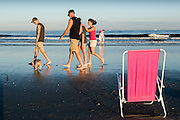 People walking on the town beach at sunseton a summer day, Narragansett, Rhode Island.