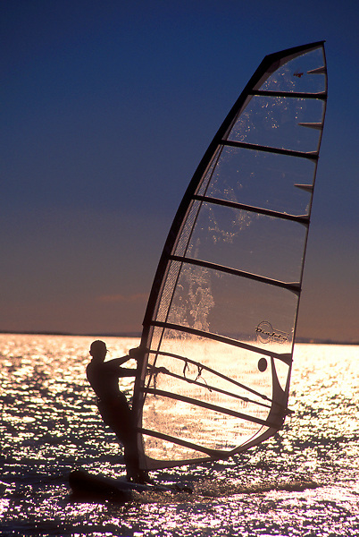 Stock photo of a man windsurfing at sunset in Galveston Texas