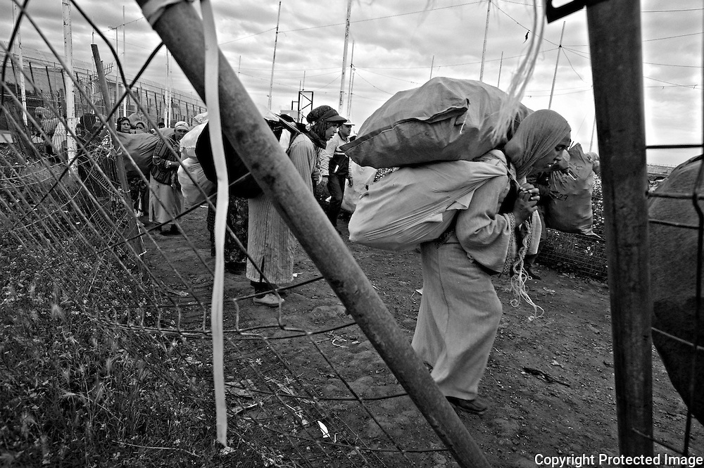 MELILLA, SPAIN - APRIL 20, 2010 : Women carrying contraband  goods up to 80 kg. in weight  queuing waiting their turn to cross  the border of  El Barrio Chino between Spain and Morocco on April 20 , 2010 in Melilla. Spain. Every day at the pedestrian border of El Barrio Chino hundreds of people are involved in transporting smuggled goods from Melilla a Spanish enclave on the North African coast to Morocco.For each package introduced in Morocco receive between 3 an 5 euros depending on size,with a little luck achieved make three trips a day.It is estimated that from Monday to Thursday on foot enter Melilla 8.000 porters, mostly women, to return to Morocco with huge sacks of goods from the warehouse border area of Beni Enzar in Melilla . ( Photo by Jordi Cami )