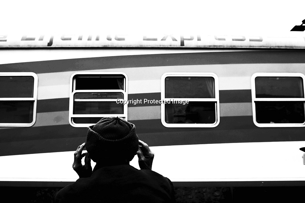 """CHONGZUO-APRIL 11: a man sits outside the """"Lifetime Express"""" train April 11, 2004 in Chongzhou, Guangxi province, China. Guangxi is one of the poorest places in China with an annual income of USD 120-250 per year for peasants. Without Lifetime Express, a Hong Kong based Non Governmental Organization (NGO) that performs cataract surgeries for free, many people in rural areas would remain partly blind as the official fee for such surgeries in China about USD 600 is out of reach for all of them."""