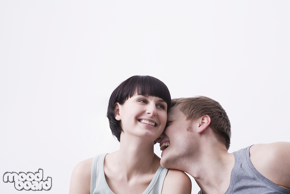 Young couple sit laughing in vest tops copyspace
