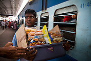 Food vendors sell Muruku, an array of South Indian snacks, through the grilled windows of the sleeper class coach to train passengers of the Himsagar Express 6318 as it stops for 20 minutes at Erode Junction stn., Tamil Nadu on 9th July 2009.. .6318 / Himsagar Express, India's longest single train journey, spanning 3720 kms, going from the mountains (Hima) to the seas (Sagar), from Jammu and Kashmir state of the Indian Himalayas to Kanyakumari, which is the southern most tip of India...Photo by Suzanne Lee / for The National
