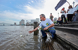 20 April 2015. New Orleans, Louisiana.<br /> Gulf South Rising.<br /> George Barisich, President of the United Commercial Fisherman's Association joins protesters to mark the 5th anniversary of the disastrous BP Macondo Well blowout in the Gulf of Mexico. Barisich throws one of 11 roses into the Mississippi to remember the 11 men who perished at sea during the blowout. The largest marine oil spill in history claimed 11 lives and witnessed an estimated 5 million barrels of oil polluting the Gulf. <br /> Photo; Charlie Varley/varleypix.com