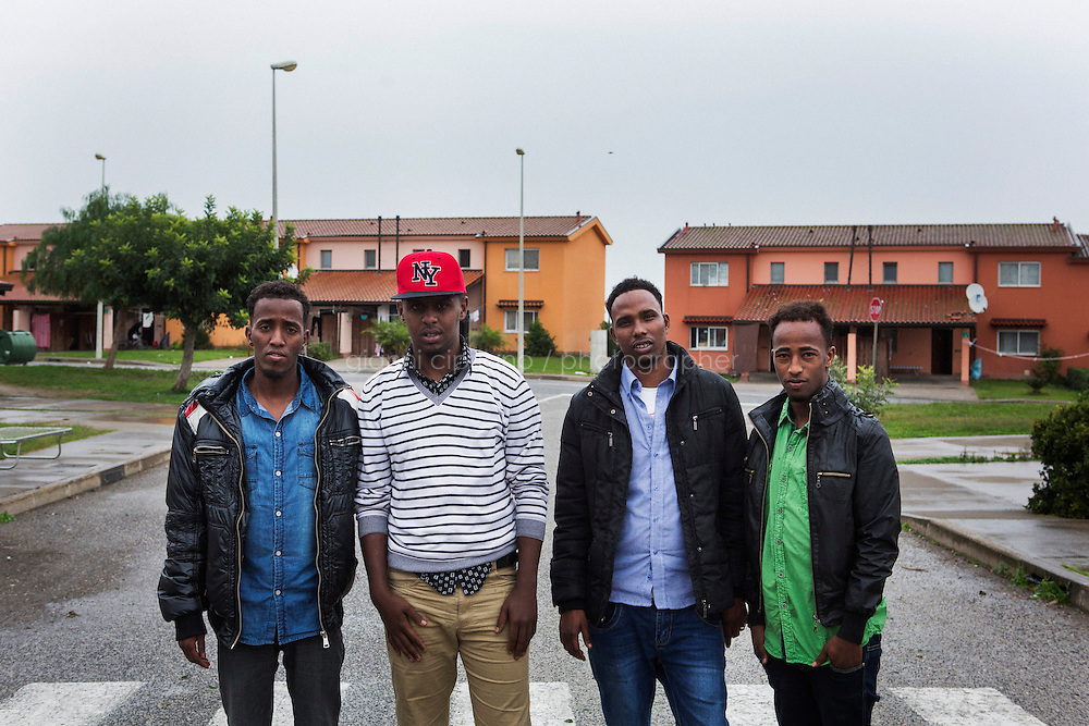 MINEO, ITALY - 26 NOVEMBER 2014: Eritrean asylum seekers pose for a group picture in a street of the CARA (Accommodation Centre for Asylum Seekers) in Mineo where approximately 4,000 asylum seekers live, in Mineo, Italy, on November 26th 2014.<br /> <br /> By law, asylum-seekers can be held for 35 days in a CARA. In reality, the average stay is closer to a year.The Cara is located at the &quot;Residence degli Aranci&quot; (Residence of the Oranges), a small town built to accomodate the families of US soldiers operating at the Naval Air Station of Sigonella 40km away. Since 2011 the &quot;Residence degli Aranci&quot; hosts the Accommodation Center for Asylum Seekers, which has since then hosted more than 12,000 seekers of 47 nationalities and over 200 ethnic groups. The CARA of Mineo includes 404 houses. Each house hosts from 7 to 11 asylum seekers.