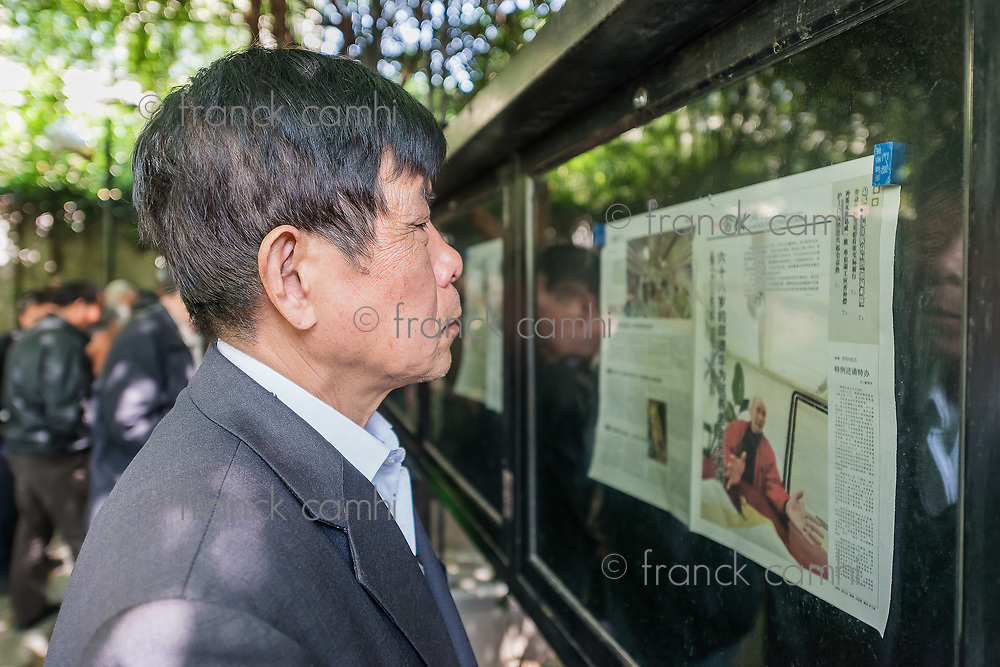 Shanghai, China - April 7, 2013: one man reading newspaper in fuxing park at the city of Shanghai in China on april 7th, 2013