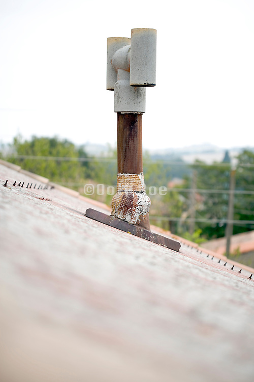 old patched up chimney on the roof of a house