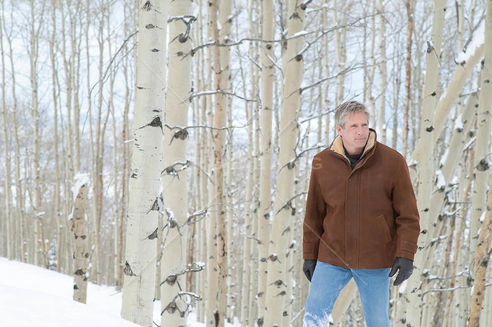 handsome man walking in the snow in an Aspen Tree Forest