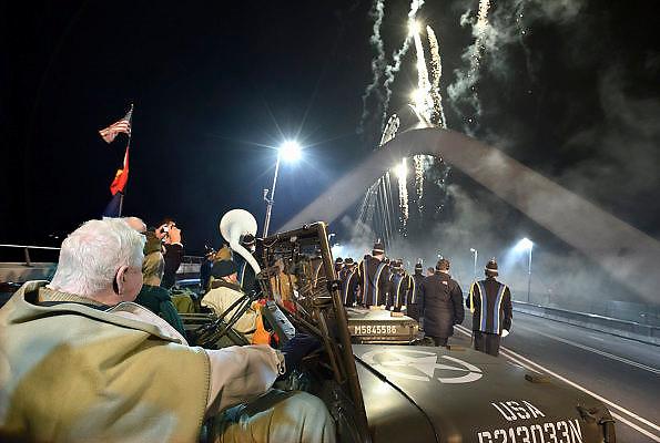 Nederland, Nijmegen, 23-11-2013Zaterdag is de nieuwe stadsbrug van de stad Nijmegen, de Oversteek, in gebruik geniomen, geopend. Dit gebeurde door het in twee jeeps afrijden van de brug van Zuid naar Noord door de twee enige nog levende veteranen van de oversteek in 1944. Op de foto kijken ze nog naar het bescheiden vuurwerk dat wordt afgestoken. De brug is vernoemd naar de heldhaftige oversteek van de rivier de Waal die Amerikaanse soldaten op dit punt maakten tijdens de operatie Market Garden in de tweede wereldoorlog om met succes de oude Waalbrug te veroveren. De overspanning is een belangrijke schakel in de ontlasting van de stad van het doorgaande verkeerDe Oversteek is een boogbrug van 285 meter lang en 60 meter hoog en is de op een na langste hoofd overspanning van Nederland, en de grootste boogbrug van Europa met een enkelvoudige boog.De brug wordt 23 november in gebruik genomen.De nieuwe oeververbinding moet zorgen voor een betere spreiding en doorstroming van verkeer binnen de stad Nijmegen. Na 75 jaar is er eindelijk een tweede vaste verbinding voor de stad. De oude waalbrug krijgt vanaf eind dit jaar groot onderhoud, waarna de volle capaciteit van beide bruggen pas gebruikt kan worden. De skyline van de stad is veranderd.De brug is een ontwerp van de Belgische architecten Ney en Paulissen. Foto: Flip Franssen
