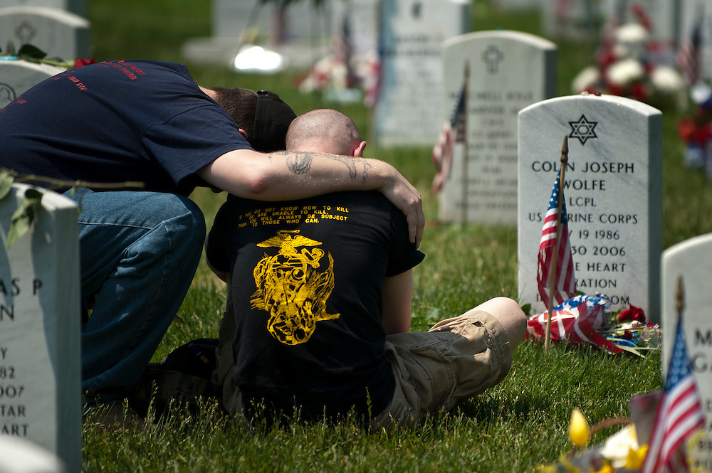 Two friends console each other near a grave in Section 60 at Arlington National Cemetery on Memorial Day 2011.