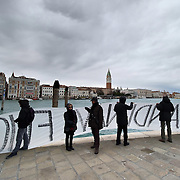 VENICE, ITALY - DECEMBER 18: Protesters on the Grand Canal hold a banner as they protest against large cruise ships in St Mark's basin on December 18, 2011 in Venice, Italy. Venetians and Environmentalists are opposed tocruise ships, which plough through the shallow Venetian lagoon, damaging the fragile buildings and canal banks.