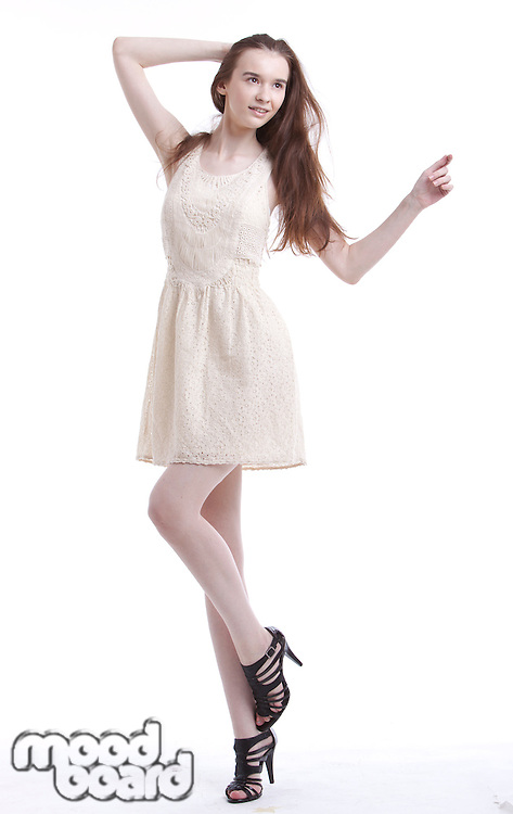 Beautiful young woman in dress with hand in her hair looking away against white background