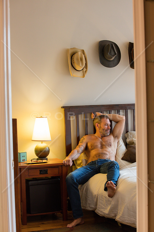 shirtless man in jeans relaxing in bed