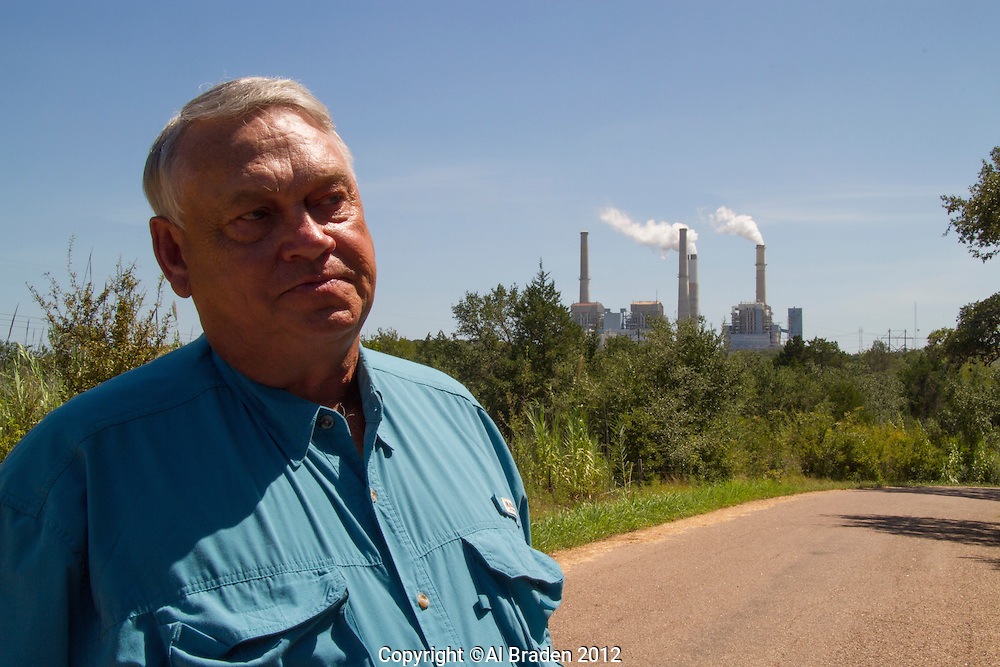 Harvey Hayek, Fayette County pecan farmer stands with Fayette Coal Plant in the background. Hayek contends that 30 years of pollution from the plant has destroyed his orchards and business.