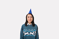 Portrait of woman wearing Christmas jumper and party hat against gray background