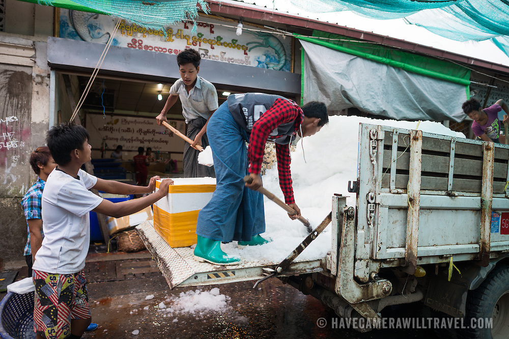 Men shovel ice from the back of a truck into buckets and coolers to deliver to the fish sellers on the street at the fish and flower market in Mandalay, Myanmar (Burma).