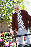Elderly man with walking frame in garden center