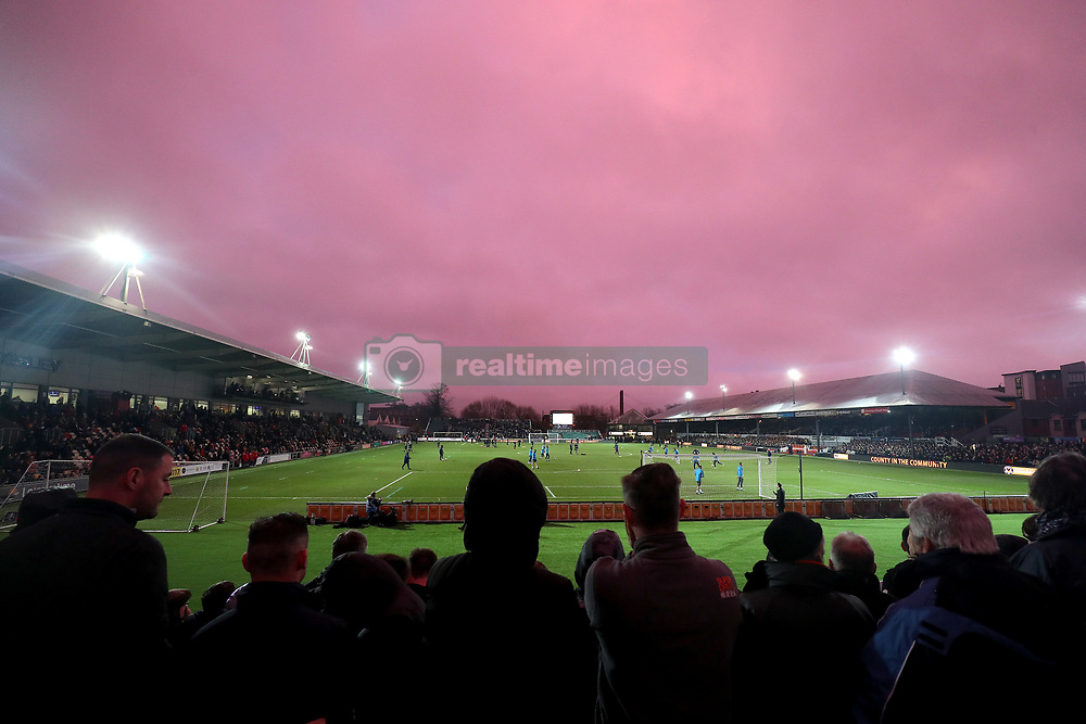 Fans in the stands watch on as Tottenham Hotspur's players warm up during the Emirates FA Cup, fourth round match at Rodney Parade, Newport.