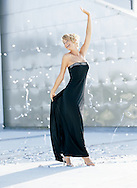 Fashion photograph of Zoe dancing in confetti, celebrating in her strapless black evening dress.