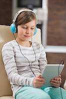 Cute girl listening music while using digital tablet at home