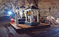 Two priests at an altar in the cave temple complex at Goa Giri Putri on Nusa Penida, Bali, Indonesia
