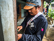 06 OCTOBER 2016 - BANGKOK, THAILAND:  A demolition worker takes apart the door frame of a home workers dismantled in Pom Mahakan. Evictions are continuing at a slow pace in Pom Mahakan Fort and as people move out their homes are destroyed to ensure new squatters don't move in. More than 40 families still live in the Pom Mahakan Fort community. Bangkok officials are trying to move them out of the fort and community leaders are barricading themselves in the fort. The residents of the historic fort are joined almost every day by community activists from around Bangkok who support their efforts to stay. City officials said recently that they expect to have the old fort cleared of residents and construction on the new park started by the end of 2016.     PHOTO BY JACK KURTZ