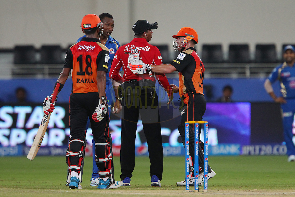 David Warner of the Sunrisers Hyderabad checks to see if umpire Kumar Dharmasena is OK after he was hit by the ball during match 20 of the Pepsi Indian Premier League Season 2014 between the Mumbai Indians and the Sunrisers Hyderabad held at the Dubai International Stadium, Dubai, United Arab Emirates on the 30th April 2014<br /> <br /> Photo by Ron Gaunt / IPL / SPORTZPICS