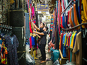 12 JANUARY 2017 - BANGKOK, THAILAND: A woman shops for clothes in Bo Bae Market. Bo Bae Market is a sprawling wholesale clothing market in Bangkok. There are reportedly more than 1,200 stalls selling clothes made in Thailand and neighboring countries. Bangkok officials have threatened to shut down parts of Bo Bae market, but so far it has escaped the fate of the other street markets that have been shut down.        PHOTO BY JACK KURTZ