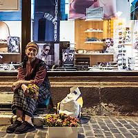 alte Frau verkauft Blumen vor einem Schaufenster in der Fußgängerzone, Kronstadt (Brasov), Siebenbürgen/Transylvanien, Rumänien * Brasov, Transsylvania, Romania
