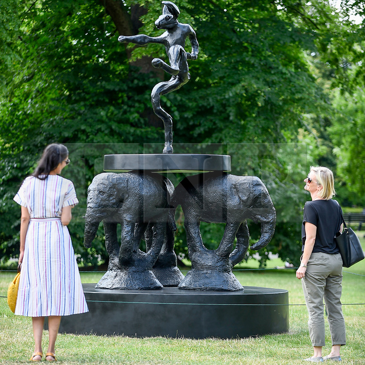 """© Licensed to London News Pictures. 03/07/2019. LONDON, UK. Women view """"Composition"""", 2008, by Barry Flanagan. Frieze Sculpture opens in Regent's Park, London's largest free display of outdoor art.  Works from 23 international artists are on display 3 July to 6 October 2019.  Photo credit: Stephen Chung/LNP"""