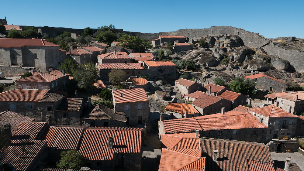 Sortelha -  Its fortified 12th-century castle teeters on the brink of a steep cliff, while immense walls encircle a village of great charms. Laid out in Moorish times, it remains a winning combination of stout stone cottages, sloping cobblestone streets and diminutive orchards.
