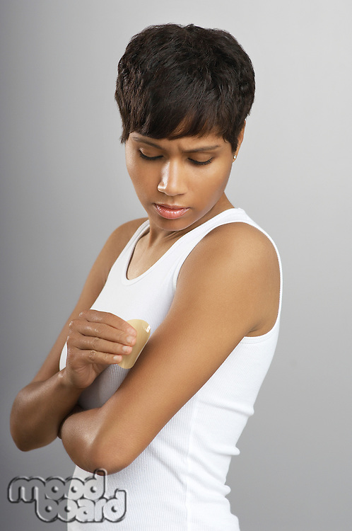 Woman applying patch to arm, studio shot