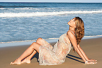 Young woman in summer dress sitting by sea side view