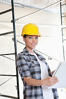Portrait of beautiful mid adult architect wearing hardhat with blueprints