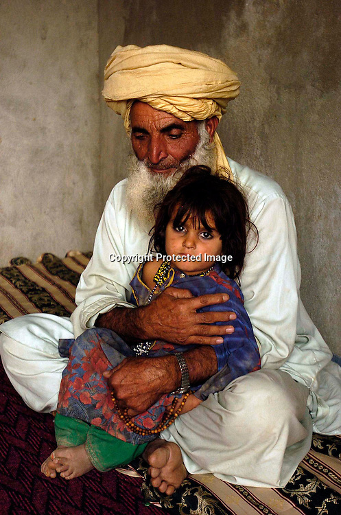 Asaldin holds Bibi Rashida(3),  the daughter  of his son Diliwar at their home in the the town of Yakubi in the district of Khost, Afghanistan May 2, 2005. Diliwar, a 22-year-old farmer and part-time taxi driver, died in December 2002 while being held in the main United States air base at Bagram, north of Kabul. His death was ruled a homicide by the Army medical examiner.<br />