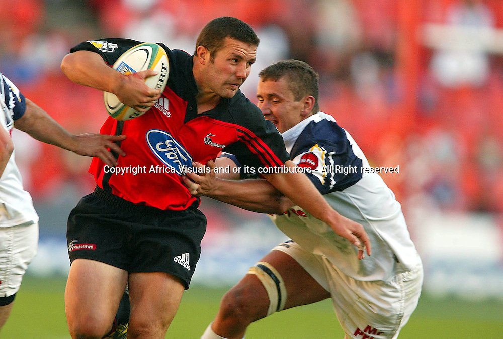 17 April, 2004. Rugby Union Super 12. Ellis Park, Johannesburg, South Africa. Cats vs Crusaders. Aaron Mauger fends off  Boela du Plooy. The Crusaders won the match 39-37, with a last minute penalty conversion.<br /> Pic: Photosport