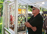 Dean Bennett, of Cedar Rapids, looks at glass artwork for sale at a booth during the 20th Annual Marion Arts Festival at City Square Park in Marion on Saturday, May 19, 2012. (Stephen Mally/Freelance)