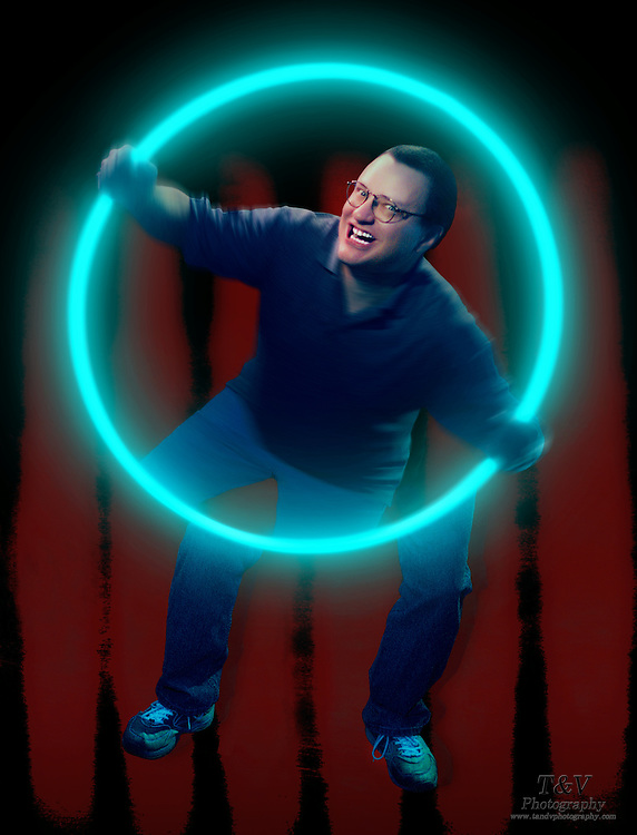 Man holding a glowing hula hoop against a red background.Black light