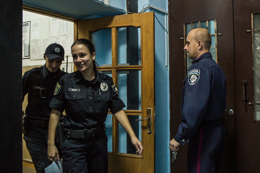 LVIV, UKRAINE - SEPTEMBER 16, 2015: Pavlo Hrupa, 31, left, and his partner Tetiana Soroka, 25, center, members of the new Lviv police, leave a police station after filling out paperwork connected to an arrest in Lviv, Ukraine. In an effort to reform the notoriously corrupt Ukrainian police force, an entirely new force has been established in several cities, including Kiev and Lviv, with a primary focus on patrolling the streets. CREDIT: Brendan Hoffman for The New York Times