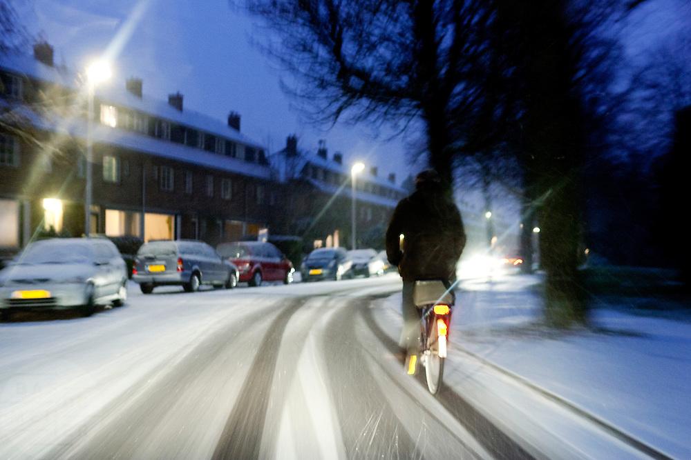 Een fietser rijdt op de Mozartlaan in Utrecht door de sneeuw.<br /> <br /> Cyclist in the snow