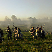Confederate troops make a quick retreat as Union soldiers advance during the  sunrise battle on Saturday during the weekend-long Battle of Perryville, a  national Civil War Reenactment, in Perryville, Ky., on 10/5/02. The sunrise  battle depicts the opening attack of Daniel Donelson's Confederate Brigade  against the center of the Union First Corps.