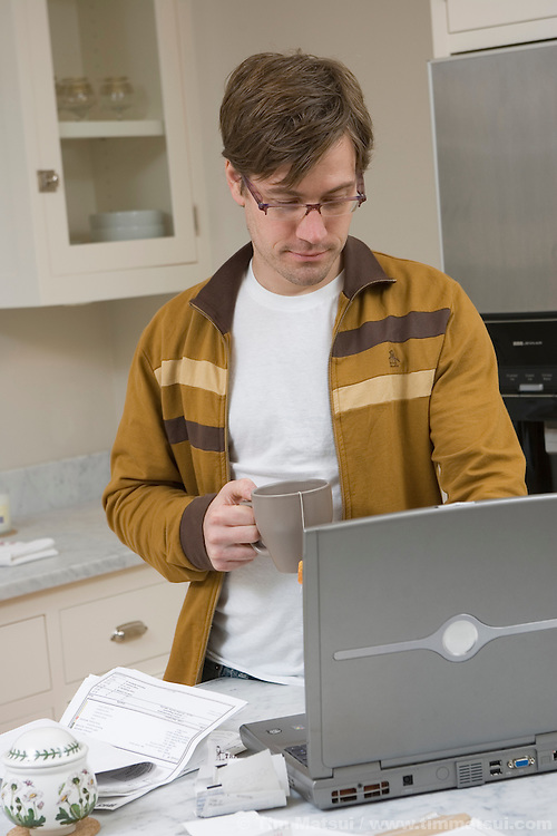 A caucasian man in his kitchen at home working on a wireless, wi-fi, laptop computer doing his household bills.