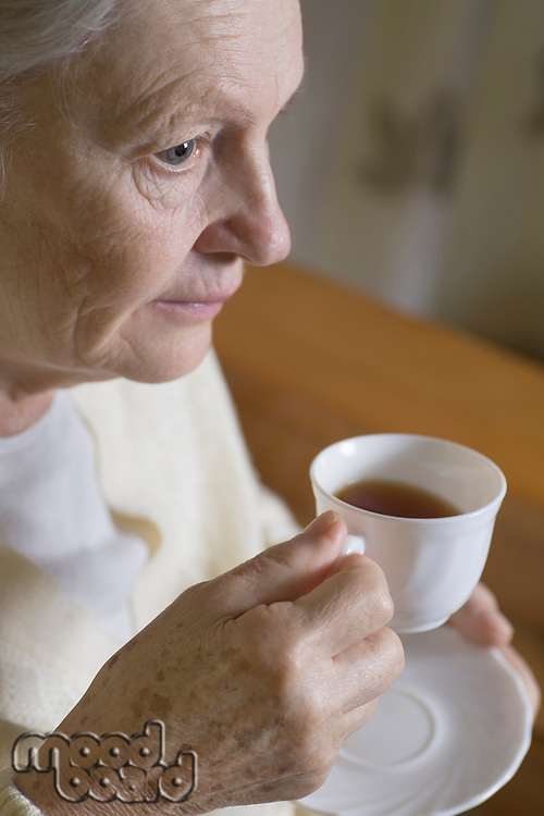 Old lady holding a cup of tea/coffe with a tea plate underneath